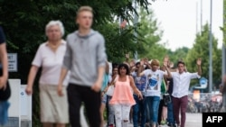 在发生袭击的现场,被疏散的人们举起双手走出购物中心(2016年7月22日)