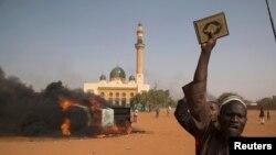 尼日尔示威者持可兰经抗议该国总统参加巴黎支持查理周刊的游行集会。
