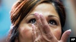 La madre de una de las víctimas del choque de un Chevy Cobalt se limpia las lágrimas mientras escucha el programa de compensaciones de GM.