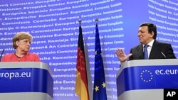 German Chancellor Angela Merkel, left, looks at European Commission President Jose-Manuel Barroso as he speaks during a news conference at the European Commission headquarters in Brussels, Oct. 5, 2011.