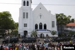 Warga berdiri di tepi jalan menyaksikan iring-iringan yang membawa jenazah Pendeta Clementa Pinckney tiba di depan gereja Emanuel AME, Charleston, South Carolina.