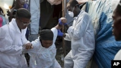 A woman suffering cholera symptoms is helped at an earthquake refugee camp in Port-au-Prince, Haiti, January 8, 2011