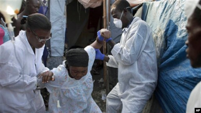 A woman exhibiting cholera symptoms is helped at an earthquake refugee camp in Port-au-Prince, Haiti on Jan. 8, 2011