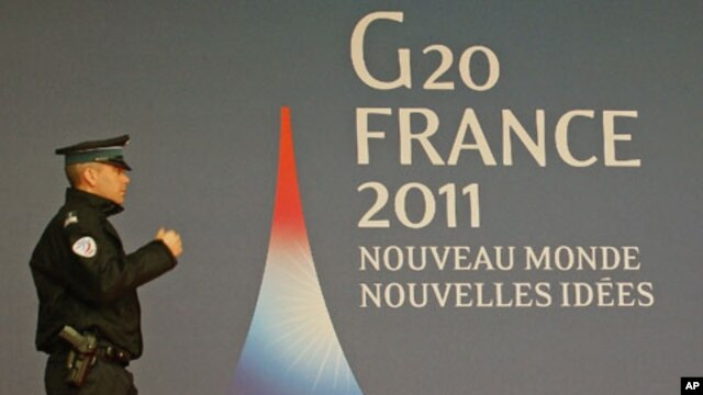 A French police officer walks past the G20 logo and slogan, 'New World, New Ideas,' outside the festival palace as preparations for the G20 summit continue in Cannes, France, November 2, 2011.