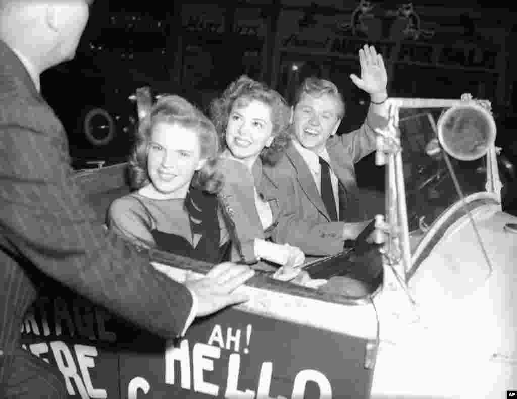Mickey Rooney, accompanied by Judy Garland and Ann Rutherford, arriving at the theater in an old Jalopy, New York City, August 17, 1941.