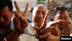 Mam Sonando (C), owner of a local independent radio station and land rights campaigner, gestures as he arrives at the Appeal Court in Phnom Penh, March 5, 2013.