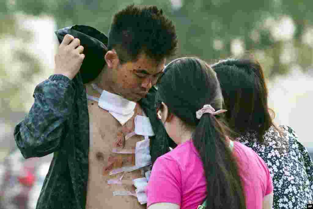 Um ferido sai do hospital onde foram encaminhadas muitas vítimas da explosão em Tianjin, China, 13 de Agosto, 2015.