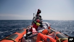FILE - Proactiva Open Arms crew conduct a search-and-rescue operation in the Mediterranean Sea, 12 nautic miles from the Libyan coast, April 13, 2017.