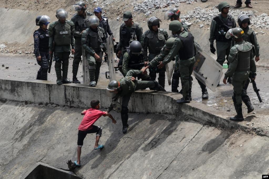 베네수엘라에서 닷새째 정전 사태가 계속되는 가운데 수도 카라카스의 강에서 어린 아이가 물을 길어나르는 것을볼라바리안 민병대가 저지하고 있다.