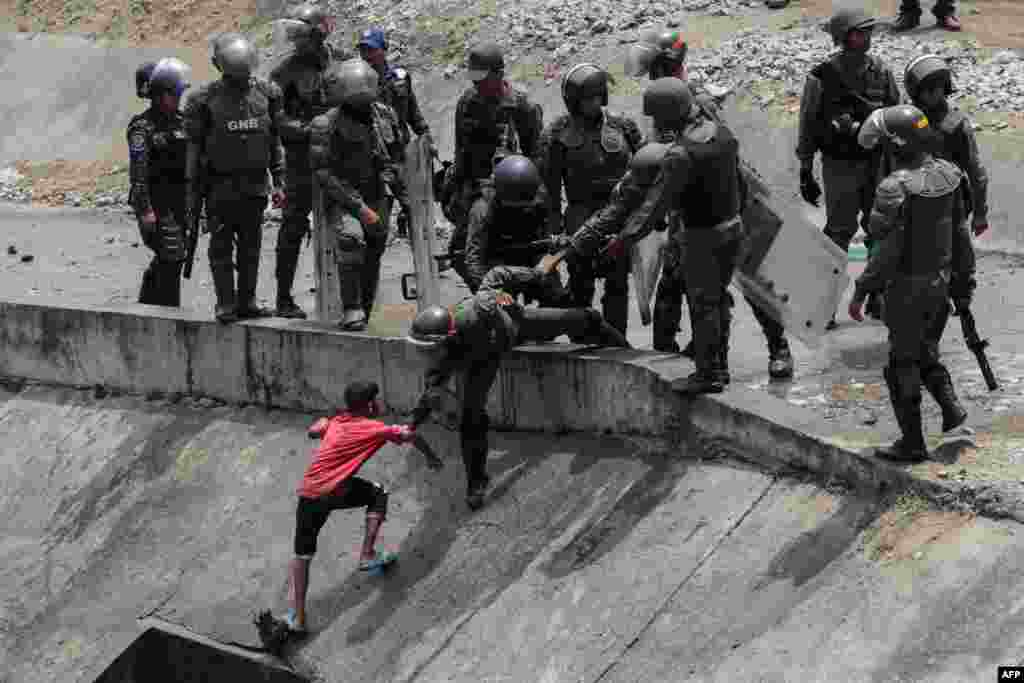 Members of the Boliviarian Guard prevent a child from collecting water from a sewage canal at the river Guaire in Caracas, as a massive power outage continues affecting some areas of the country.