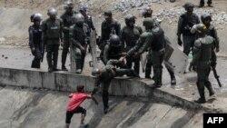 Pripadnici bezbednosnih snaga pokušavaju da spreče dete da uzme vodu iz odvoda za kanalizaciju u Karakasu