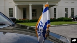 FILE - An Israeli flag is seen on one of the vehicles in Israeli Prime Minister Benjamin Netanyahu's motorcade during one of his meetings with President Barack Obama at the White House in Washington.