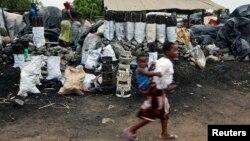 Children walk past charcoal sellers in Kitwe, Zambia, Jan. 17, 2015.