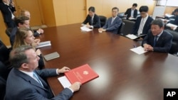FILE - Britain's Secretary of State for International Trade Liam Fox, bottom left, and Japanese Minister of Economic Revitalization Toshimitsu Motegi, right, attend a meeting in Tokyo July 31, 2018. (AP Photo/Eugene Hoshiko)