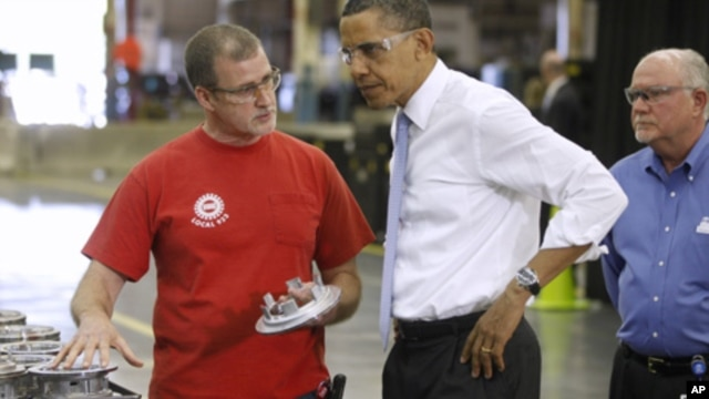President Barack Obama talks with employees Mike Clements, right, and Richard Thomas during a tour at Allison Transmission in Indianapolis, Ind., May 6, 2011.
