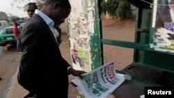 Wani mutum yana kallon jarida a Abuja.