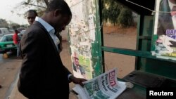 FILE - A man looks at a newspaper at a news stand in Abuja. Nigeria's military repelled multiple attacks by suspected Boko Haram militants on Borno state capital Maiduguri, Jan. 26, 2015.