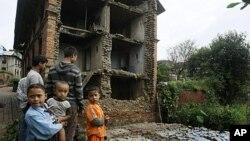 尼泊尔的孩子们站在被喜马拉雅地区地震震毁的房子旁