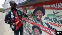 A man points to campaign posters of Nigerian President Goodluck Jonathan and candidate of the ruling People's Democratic Party (PDP) in Lagos, Nigeria, March 21, 2015.