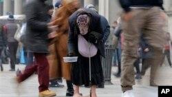 Seorang perempuan mengemis di antara orang lewat di jalanan kota Milan (Januari 2013). Ekonomi zona Euro masih lemah dan pengangguran terus meningkat.