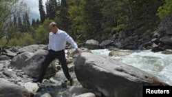FILE - During a visit to Kyrgyzstan, Russia's President Vladimir Putin crosses a stream in Ala-Archa National Park, south of Bishkek, May 28, 2013.