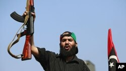 A Libyan rebel fighter celebrates as they drive through Tripoli's Qarqarsh district, August 22, 2011