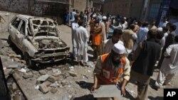 Dân chúng đến xem vụ nổ bom bên ngoài văn phòng của ứng cử viên ơ Peshawar, Pakistan, 28/4/13