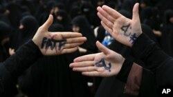 سخت گیر ایرانی مظاہرین نے اپنے ہاتھوں پر لکھا ہے: ''ہم ایف اے ٹی ایف کو نہیں مانتے''۔ (فائل فوٹو)