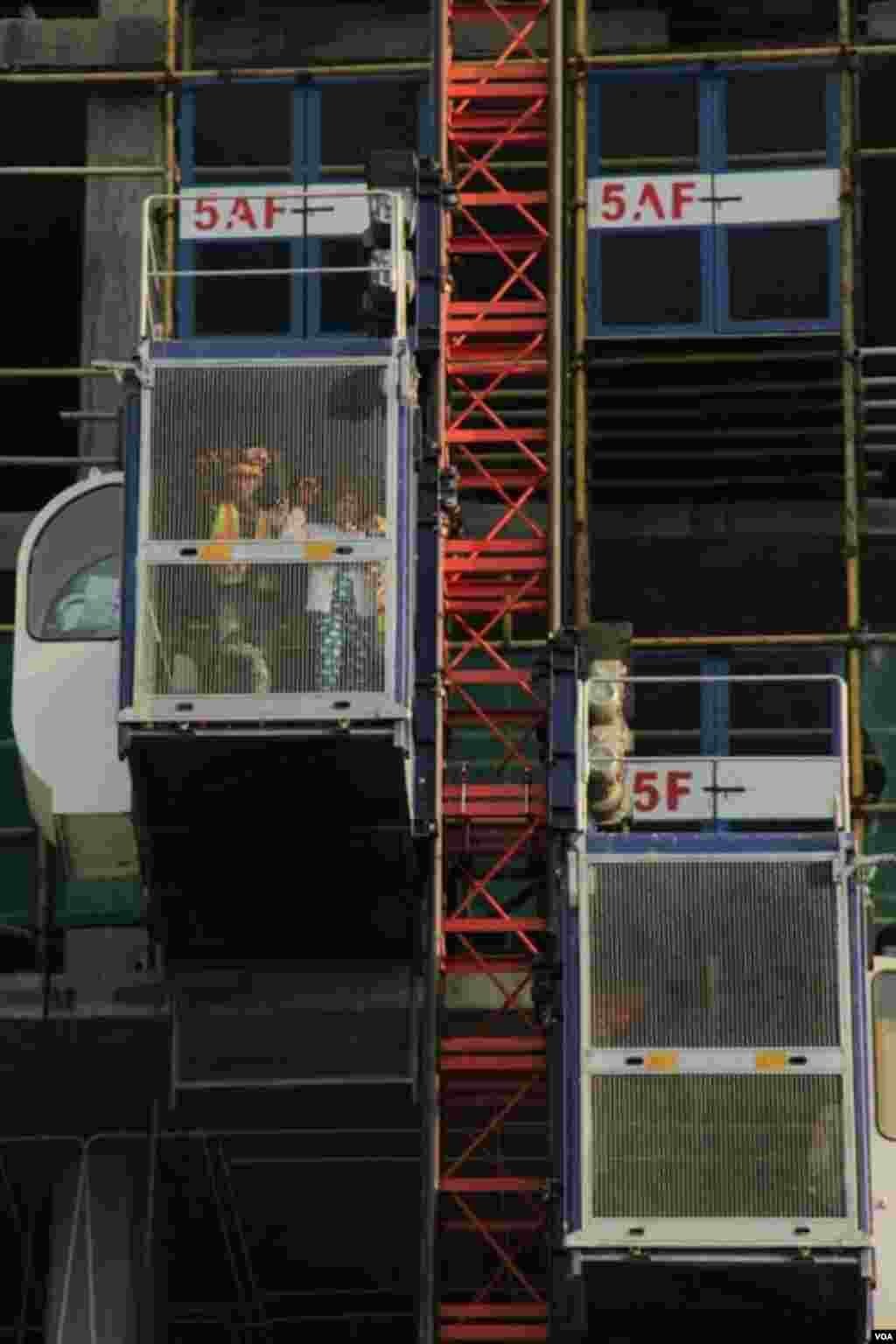 Workers look down from an elevator at the construction site of Olympia City, September 29, 2014. (Nov Povleakhena/VOA Khmer)