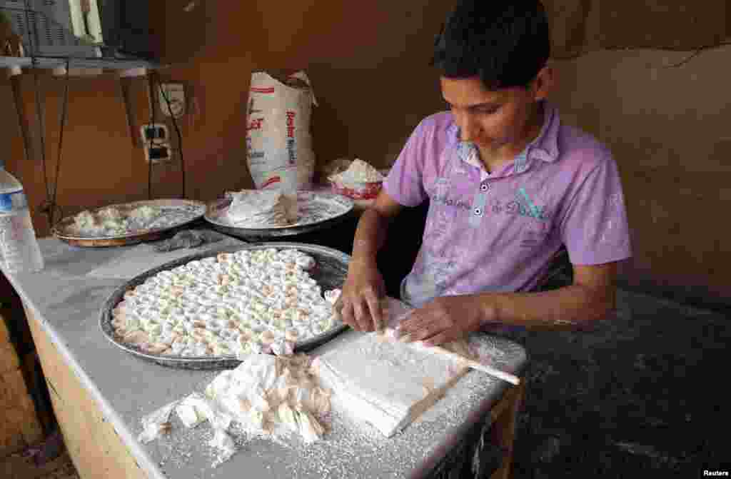 A boy makes pastry at a shop in Darkush town, Idlib province, May 26, 2013.