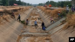 FILE - In this March 28, 2016 photo, Thai workers repair a dried up irrigation canal at Chai Nat province, Thailand. Much of Southeast Asia is suffering its worst drought in 20 or more years. (AP Photo/Sakchai Lalit)