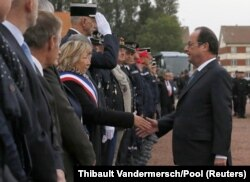 法國總統奧朗德週一訪問港口城市加來時,與加來市長握手。