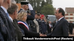 "French President Francois Hollande (R) shakes hands with the mayor of Calais, Natacha Bouchart, during a meeting with officers of the French Gendarmerie in Calais as part of his visit to the northern French port which is home to the ""Jungle"" migrant camp, France, Sept. 26, 2016."