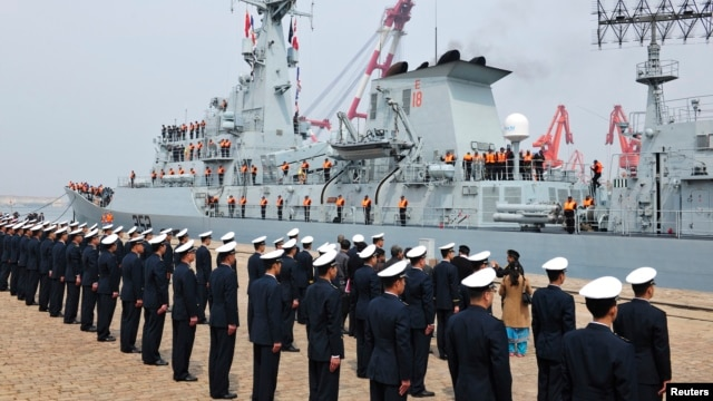 Chinese navy officers (backs to camera) stand in formation as Pakistan naval frigate Shamsher arrives at a military port before a maritime drill during the Western Pacific Naval Symposium in Qingdao, Shandong province, April 20, 2014.