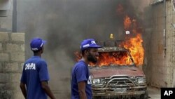 Pakistani volunteers look at a vehicle that was set on fire by an angry mob in Karachi, Pakistan, August 1, 2011