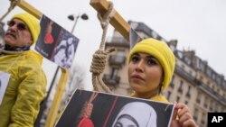 Một người biểu tình chụp hình với sợi dây thừng quanh cổ khi những người Iran đối lập tuần hành phản đối hành quyết tại Iran trong khi Tổng thống Iran Hassan Rouhani ở Pháp trong một chuyến thăm chính thức kéo dài hai ngày tại Paris, thứ Năm ngày 28 tháng 1 năm 2016.