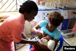 FILE - A nurse helps out a mother who nearly gave birth to a premature baby on her breastfeeding at Kisenyi health centre in Uganda's capital Kampala, Apr. 10, 2015.