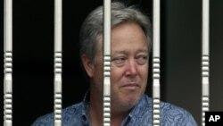 Чип Старнс смотрит из окна завода, где он удерживается в качестве заложника. Пригород Пекина, Китай. 25 июня 2013 г.
