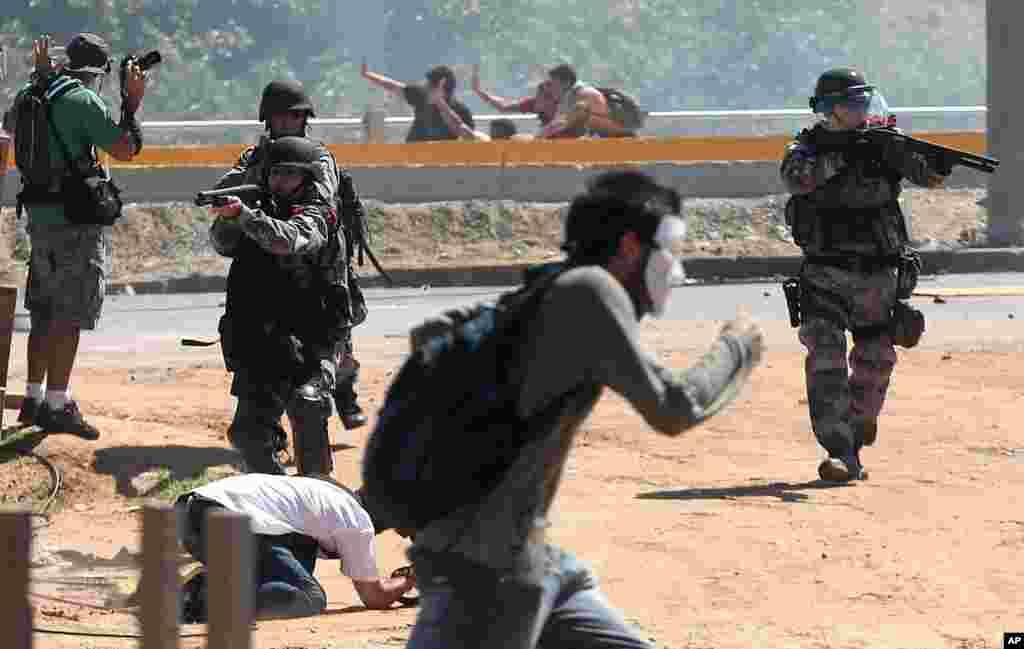 Cảnh sát chống bạo động Brazil chĩa súng vào người biểu tình gần sân vận động Castelao, ngày 19/6/2013.