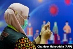 Seorang petugas kesehatan bersiap untuk memberikan vaksin Sinovac di Rumah Sakit Zainoel Abidin di Banda Aceh pada 21 Januari 2021. (Foto: AFP/Chaideer Mahyuddin)