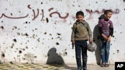 "A Syrian boy holds a toy gun as he plays soccer with others between destroyed buildings with graffiti that reads ""Syria al-Assad,"" in the old city of Homs, Syria, Friday, Feb. 26, 2016."