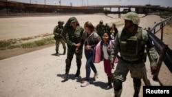 Miembros de la Guardia Nacional de México escoltan a una mujer nicaraguense y su hija después de detenerlas cuando intentaban cruzar ilegalmente la frontera entre los Estados Unidos y México, en Ciudad Juárez, México, 21 de junio de 2019. REUTERS / Jose Luis Gonzalez.