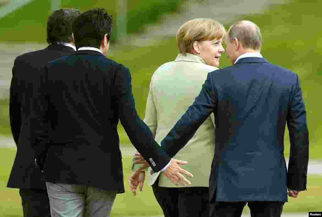 Japan's Prime Minister Shinzo Abe (2nd L) touches hands with Russia's President Vladimir Putin as they walk with Germany's Chancellor Angela Merkel, after a G8 summit group photograph was taken at the Lough Erne golf resort in Enniskillen, Northern Ireland.