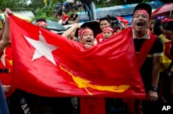 Supporters of Myanmar's National League for Democracy party brave rain outside the NLD headquarters in Yangon, Myanmar, Nov. 9, 2015.