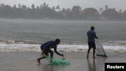 28일 인도 케랄라의 포트 코치 해변에 갑작스러운 폭우가 쏟아진 가운데 어부들이 어물망을 던지기 위해 준비하고 있다.