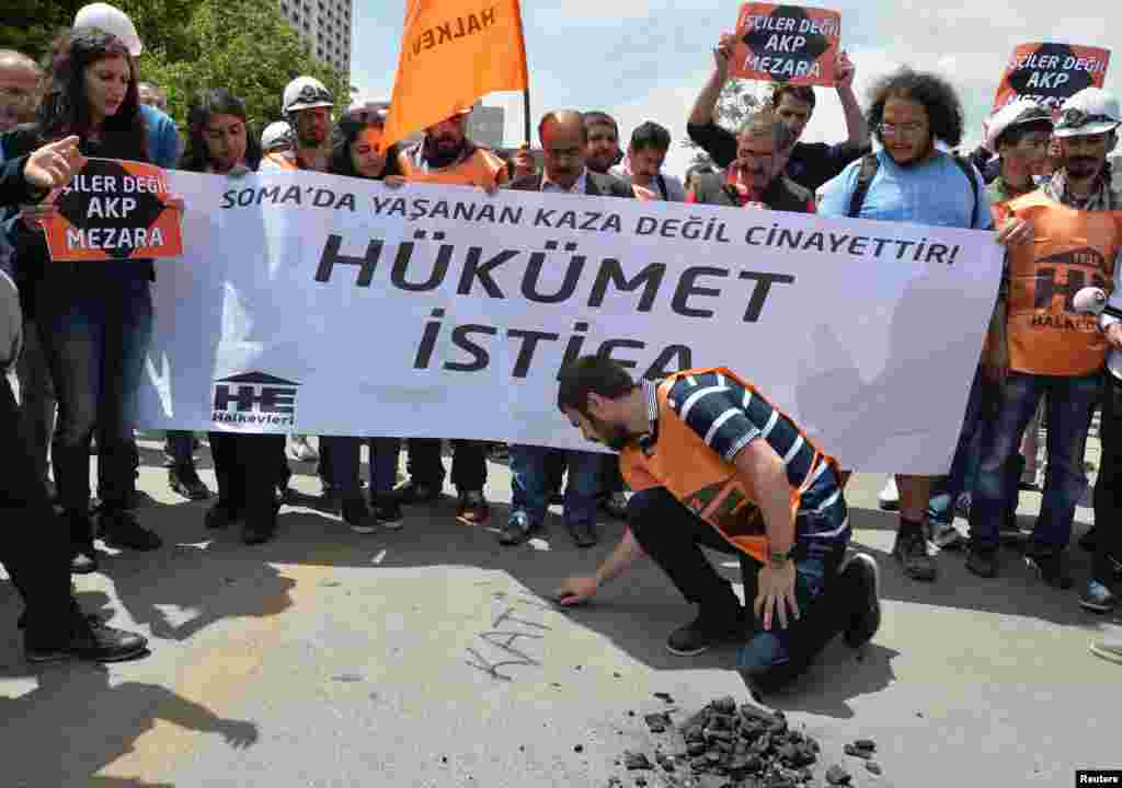 "A protester writes ""murderer"" with piece of coal on the ground as they demonstrate to blame the ruling AK Party (AKP) government on the mining disaster in western Turkey, in Ankara May 14, 2014. Rescuers pulled more dead and injured from a coal mine in we"