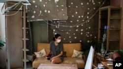Rachelle Boumelhem sits in her damaged beauty salon in Beirut, Lebanon, Monday, Aug. 10, 2020.