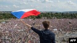 یک مرد با پرچم جمهوری چک در مقابل دهها هزار معترض شهر پراگ.