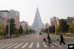 Warga mengenakan masker saat melintasi jalan di depan Hotel Ryugyong di Pyongyang, Korea Utara, 28 April 2020. (AP Photo/Cha Song Ho)