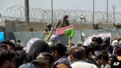 """FILE - U.S. soldier holds a """"Gate Closed"""" sign as hundreds of people gather near an evacuation checkpoint on the perimeter of Hamid Karzai International Airport, in Kabul, Afghanistan, Aug. 26, 2021."""